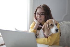 Woman with a beagle at a laptop. Photo by Andrea Piacquadio from Pexels