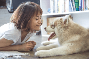 A smiling woman giving attention to a husky puppy
