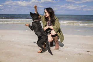 A woman playing with a brown and black dog on a beach