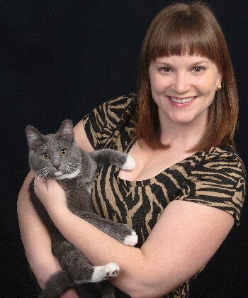 A gray tuxedo cat held by his smiling handler