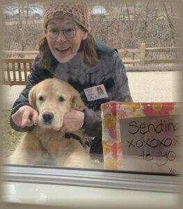 A therapy animal team makes a visit through the window of a facility