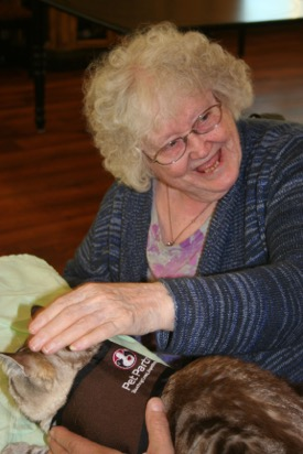 A smiling senior woman pets a therapy cat