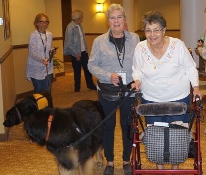 Seniors walking with therapy dog teams in the hallway of a facility