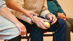 The hands of a caregiver and a senior preparing to throw a ball for a therapy dog