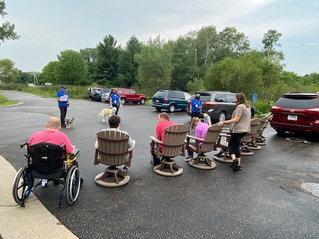 A group of residents at a care facility sitting outside and learning from therapy dog teams