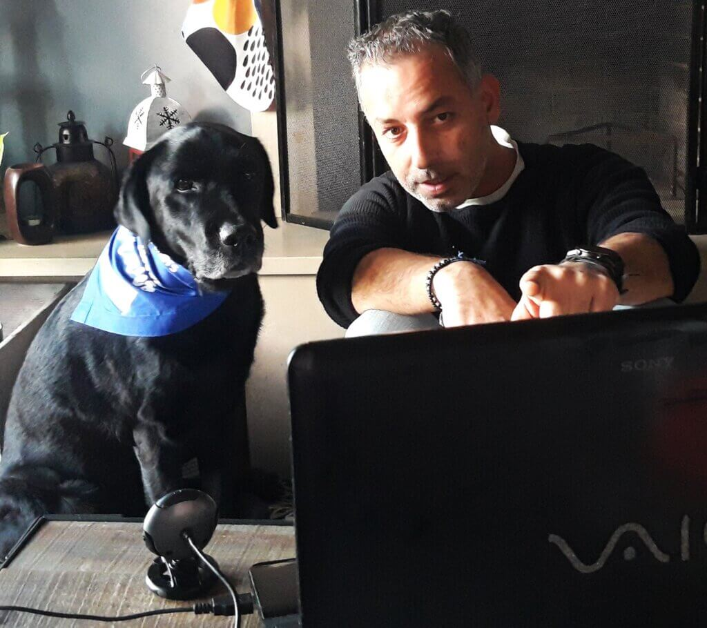 A black lab therapy dog and his handler in front of a laptop and webcam for a virtual visit