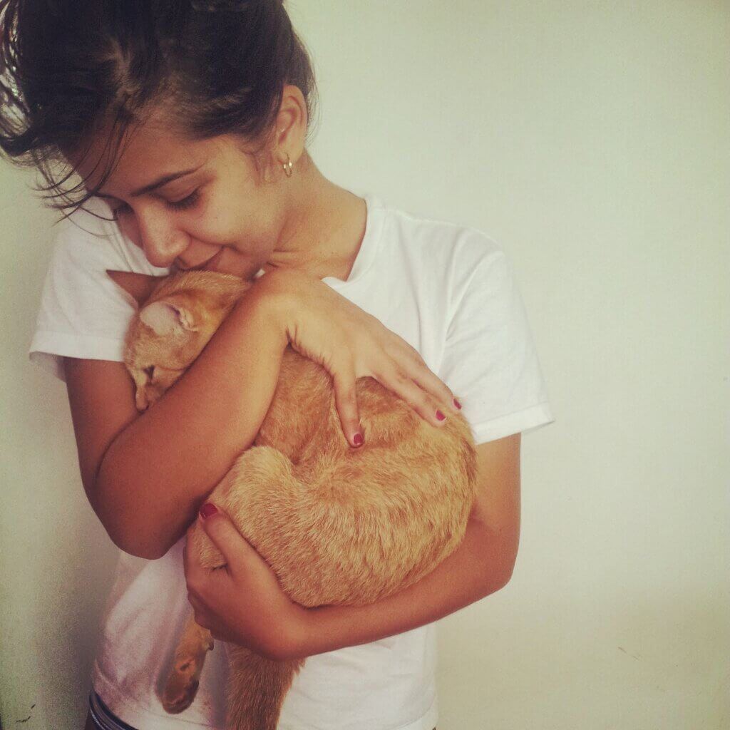 A tween girl holding and cuddling an orange tabby cat