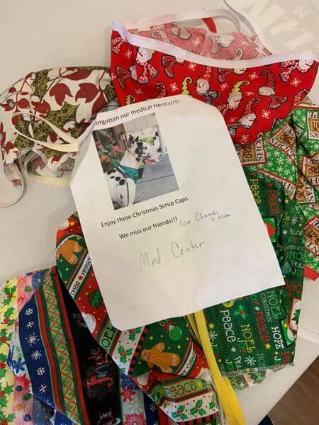 """Christmas-themed surgical caps with a note that reads """"We haven't forgotten our medical heroes! Enjoy these Christmas scrap caps. We miss our friends! Love, Chance & Marcia. There is also a picture of a great Dane therapy dog on the note."""