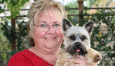 A smiling woman holding a Norwich terrier