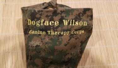 "A dog scarf with a digital camo pattern and embroidery reading ""Dogface Wilson Canine Therapy Corps"""
