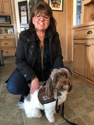 Beau, a brown and white Havanese therapy dog, wearing a Pet Partners vest, with his handler Judy behind him.