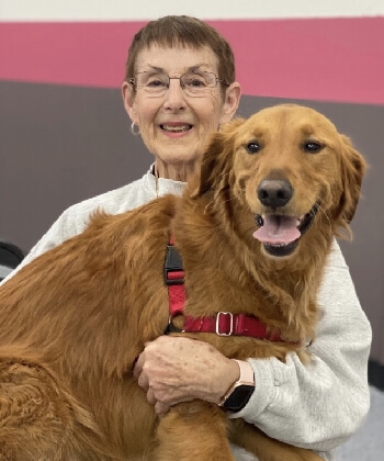A smiling woman holding a happy golden retriever