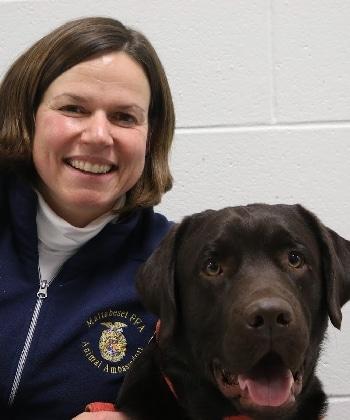 A smiling woman and a happy chocolate Labrador retriever