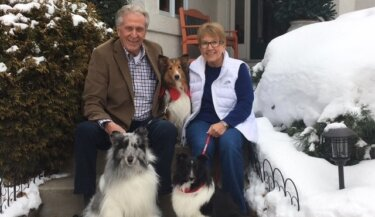 A smiling man and woman sit in front of a house with three Shetland sheepdogs