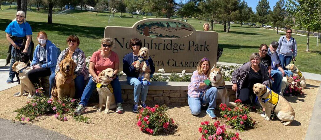 Guide dogs in training and their handlers pose with several Pet Partners therapy dog teams in front of a park sign after a walk.
