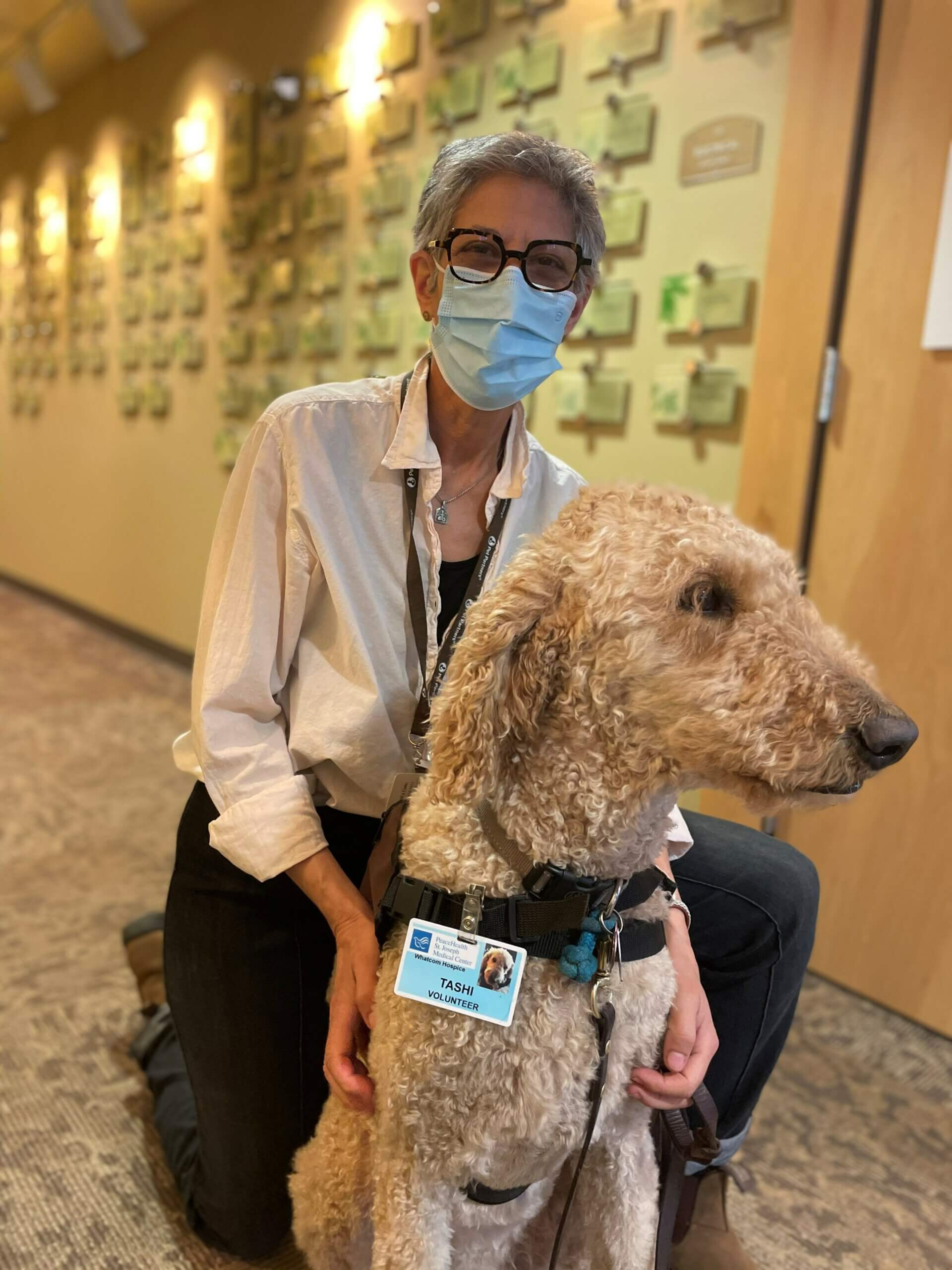 A therapy animal handler and her therapy dog in a common space at a hospice facility