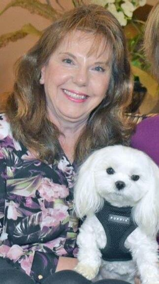 A therapy dog handler with her maltese therapy dog