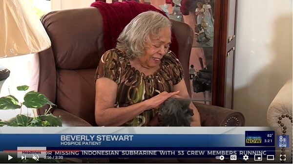 Screen shot from a news story showing a hospice patient holding a small therapy poodle