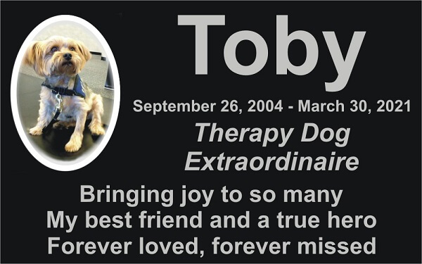 """A memorial card with a photo of a therapy dog and text reading """"Toby September 26-2004-March 30, 2021 Therapy Dog Extraordinaire Bringing joy to so many, My best friend and a true hero, Forever loved, forever missed"""""""