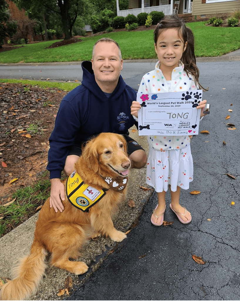 A man, a golden retriever, and a young girl posing with their World's Largest Pet Walk walker bib