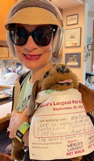 """A woman holding a dachshund puppet that is wearing a World's Largest Pet Walk walker bib, which says, """"I am walking with my husband Lee in honor of our dachshund Jasmine. We were a Pet Partners team for 6 years."""""""