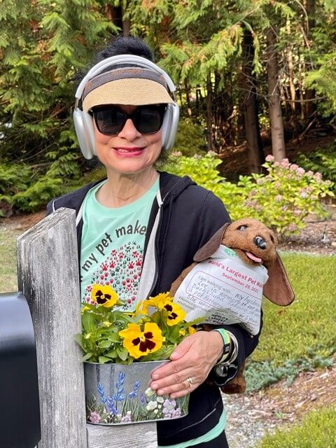 A woman wearing a World's Largest Pet Walk T-shirt and carrying a dachshund puppet that is wearing a World's Largest Pet Walk walker bib.